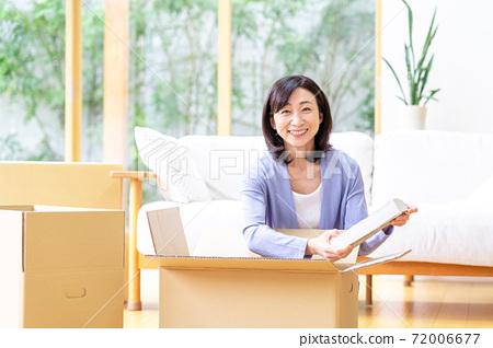 包裝在紙板在客廳裡的中年女人 72006677