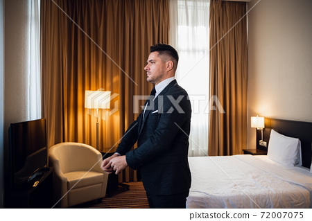 Young handsome businessman adjusting his jacket, dressing up at 72007075