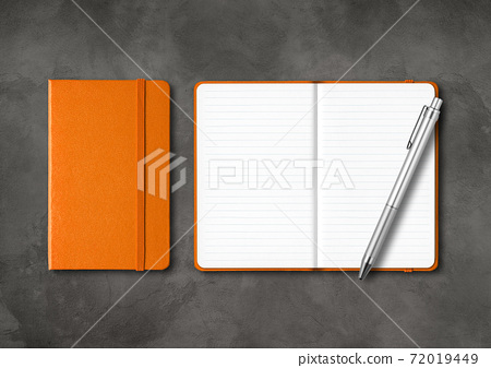 Orange closed and open lined notebooks with a pen on dark concrete background 72019449