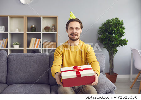 Young positive man in festive clown hat sitting on sofa and showing holiday present box 72023330