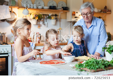 Family and kids cooking pizza in cozy home kitchen. Grandmother and three sisters preparing homemade italian food 72025653