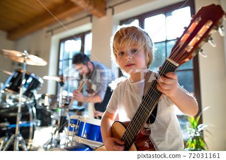 Portrait of small boy with father indoors at home, playing drums and guitar. 72031161