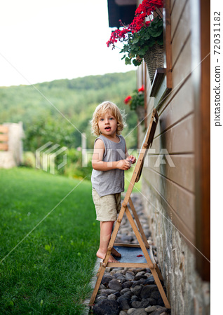 Happy small blond boy playing outdoors by house in summer. 72031182