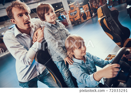 Dad and sons playing slot machines in center.  72033291