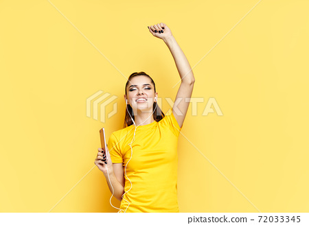 Cheerful young woman listening to music with headphones and dancing enjoy favourite songs 72033345