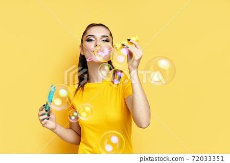 Happy beautiful woman blowing soap bubbles 72033351