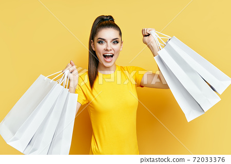 Happy excited shopaholic woman with shopping bags in hands enjoy her shopping 72033376