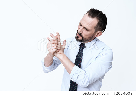 A man looks at his hand and feels severe pain. 72034008