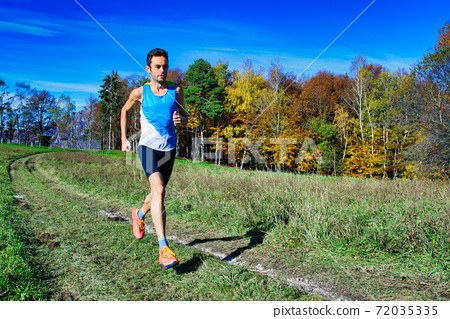 Running athlete during a workout among hillside meadows and woods 72035335