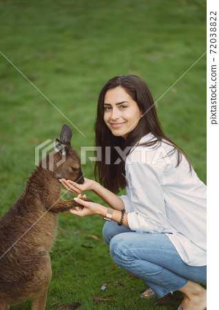 Woman in the reserve is playing with a kangaroo 72038822