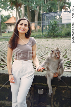 Woman on vacation playing with a monkey 72038879