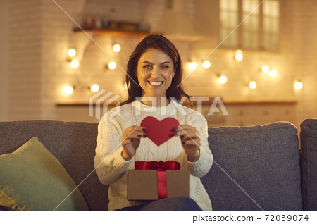 Smiling woman sitting with a gift and showing a red heart to the webcam during a video call. 72039074