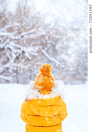 Back view of young woman wearing yellow jacket walks in snowy park 72041397
