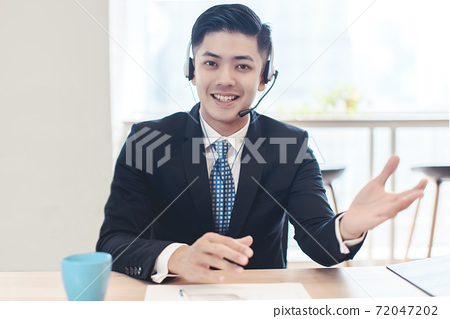 Head shot portrait confident young businessman  looking at camera and talking by headphone. 72047202
