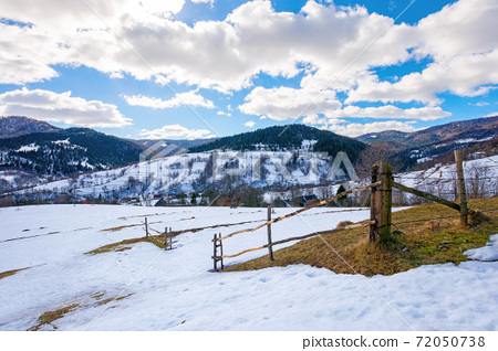 mountainous rural landscape on a sunny winter day. fields and trees on rolling hills covered in snow. fluffy clouds on the sky. beautiful carpathian landscape 72050738
