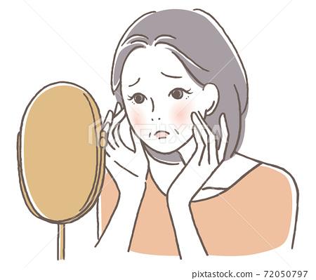 Senior woman worried looking in the mirror 72050797