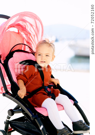 2-year old girl in a terracotta dress and white tights sitting in a pink stroller 72052160