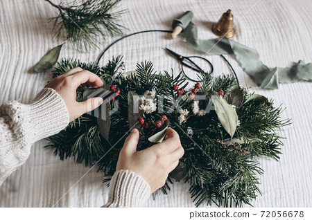 Christmas moody still life. Closeup of women hands crafting advent floral hoop wreath. Garland of fir, eucalyptus. Pine tree branches. Vintage scissors and bell on muslin table cloth. Selective focus. 72056678