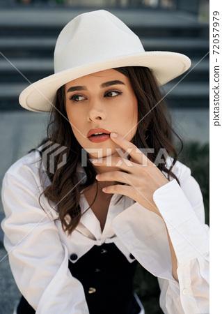 Gorgeous model wearing white hat posing in city. 72057979