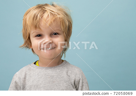 boy on a blue background, close-up portrait of a child with beautiful hair and a mischievous smile 72058069