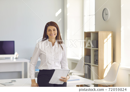 Smiling business woman standing in her office, holding notebook and looking at camera 72059824