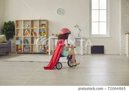 Preschool girl in helmet and red cape riding her tricycle in a cozy nursery room 72064865