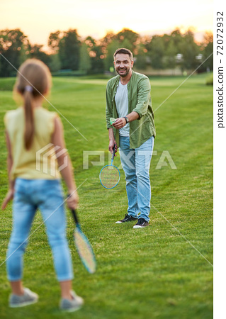 Full length shot of happy father playing badminton with his little daughter outdoors in the park on a summer day 72072932