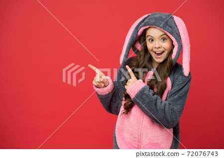Take a look. Happy girl pointing index fingers at something. Small child 72076743