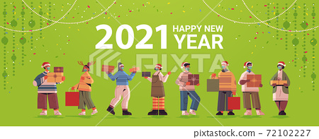 people in santa hats holding gifts mix race men women celebrating 2021 new year and christmas holidays 72102227