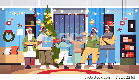 multi generation family in santa hats holding gifts new year christmas holidays celebration concept 72102263
