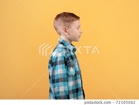 Ginger boy with closed eyes posing on yellow background 72105082