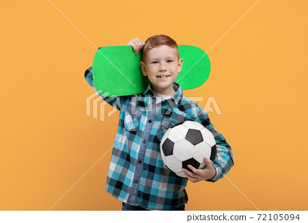 Boy posing with soccer ball and skateboard on yellow 72105094