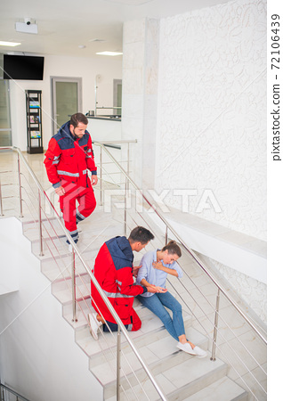 Two medical workers in red uniform coming to a woman on the stairs 72106439