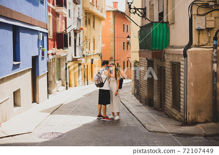 Couple with face masks on a pintoresque small village 72107449