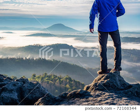 Man watch thick mist in valley from rocky view point 72108344