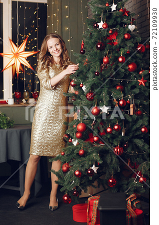 Woman in a gold dress in a christmass decorations 72109930