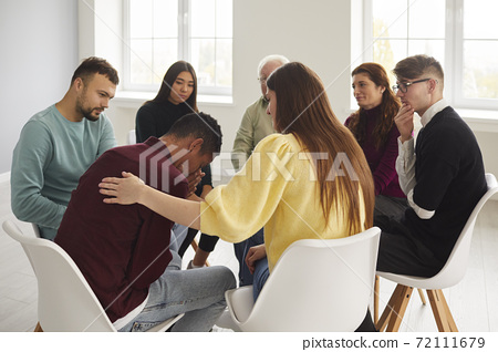Diverse people supporting and comforting crying young man in group therapy session 72111679