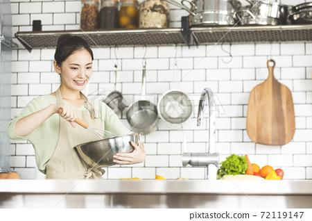在廚房裡做飯一個微笑的女人 72119147