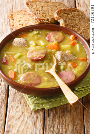 Snert Split Pea Soup with vegetables,  smoked sausages and pork closeup in the plate. vertical 72136891