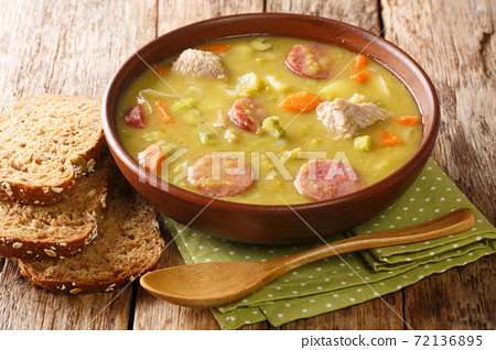 Winter pea soup with vegetables, sausages and pork close-up in a bowl. horizontal 72136895