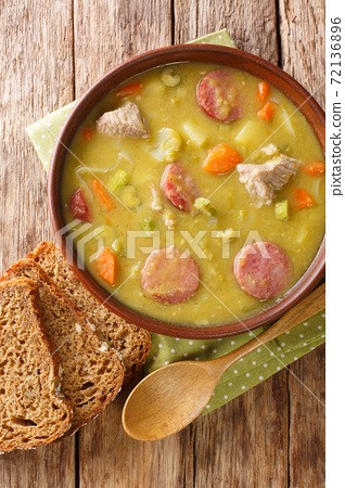 Dutch Split Pea Soup Erwtensoep with vegetables, sausages and pork closeup in the plate. vertical top view 72136896
