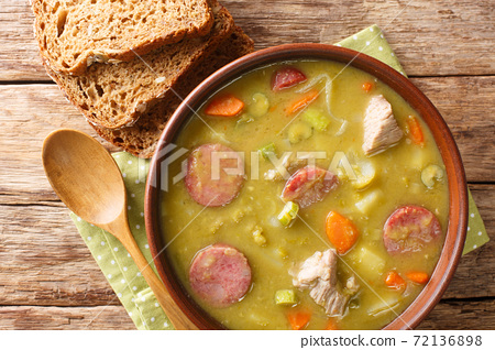 Delicious split green peas soup with vegetables, sausages and pork close-up in a bowl. horizontal top view 72136898
