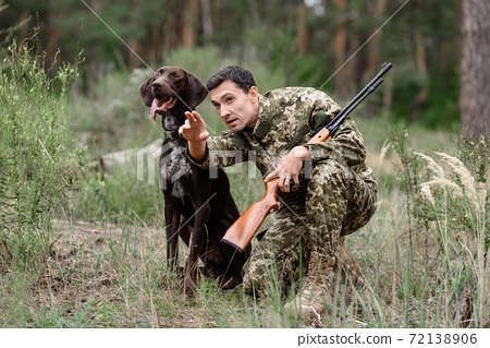 Man with Rifle and Pointer Dog Hunting for Rabbit. 72138906