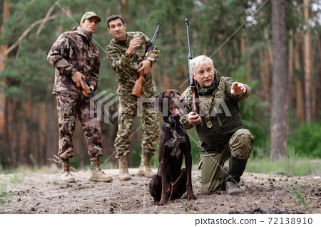 Man Hunter Pointing Somewhere for Hunting Dog. 72138910