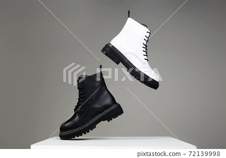 Black and white boots in the air. fashion shoes still life 72139998