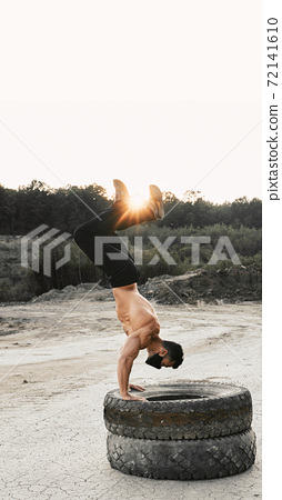 Bodybuilder in mask doing exercises for arms on tyres 72141610