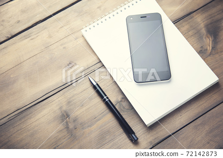 phone on notebook and pen 72142873
