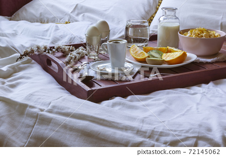 Romantic Breakfast in bed with spring flowers. Window light, copy space 72145062