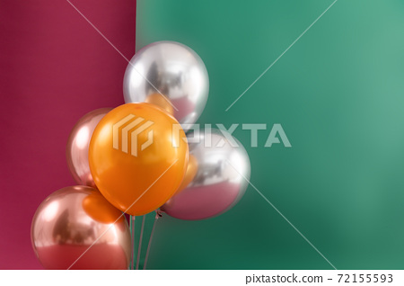 Bunch of metallic balloons floating on dark red and green background 72155593