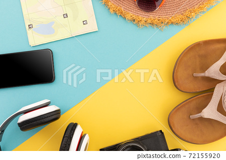 Sunglasses, flip flops, sunhat, map and smartphone on yellow and blue 72155920